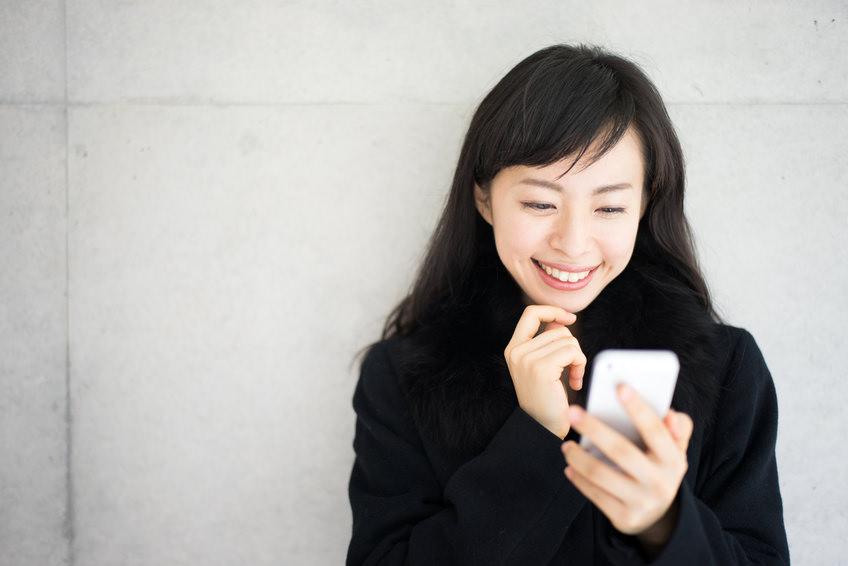 笑顔でスマホを操作する女性